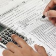Person completing 1040 tax form with calculator...