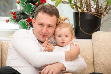 Photo pour Joyeux père et bébé fille câlins à la maison. Utilisez-le pour un concept d'enfant, de rôle parental ou d'amour - image libre de droit