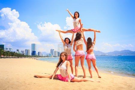Photo pour Pom-pom girls en uniforme rose blanc effectuer High Straddle Stunt sur la plage de sable contre la mer - image libre de droit