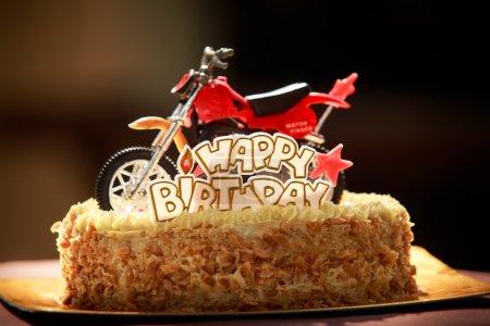 Photo pour Gâteau d'anniversaire avec des noix et de la crème vanille décoré avec figurine de moto, étoiles rouges et mots Joyeux anniversaire - image libre de droit