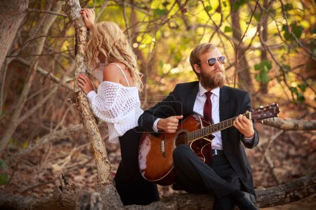 Woman and man with guitar in tropics