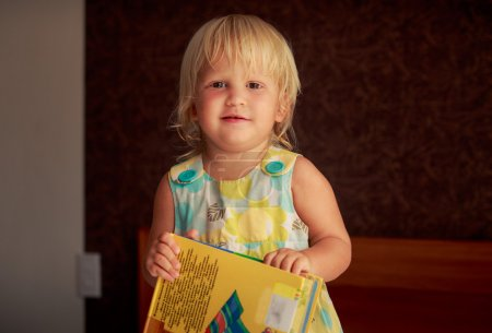 girl plays with  childish book