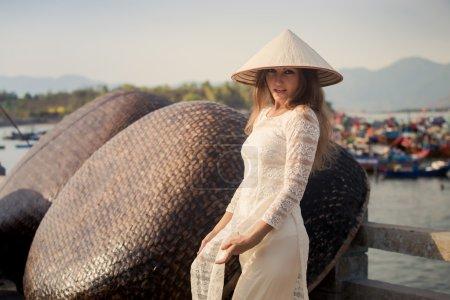 girl in Vietnamese dress  by barrier