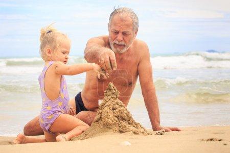 Photo pour Grand-père barbu, petite fille blonde avec queue de cochon et garçon en chapeau construire château de sable sur la plage par vagues surf - image libre de droit