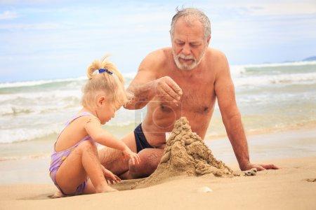 Grandpa  and children  Building Sand Castle