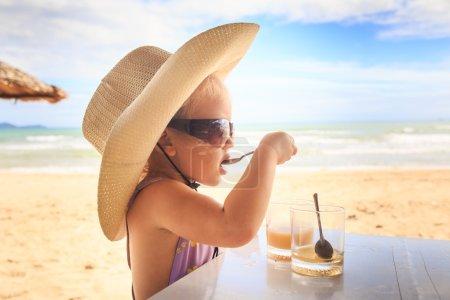 Photo pour Gros plan portrait petite blonde mignonne fille en grande paille chapeau lunettes de soleil boissons jus avec cuillère à thé à table sur la plage - image libre de droit