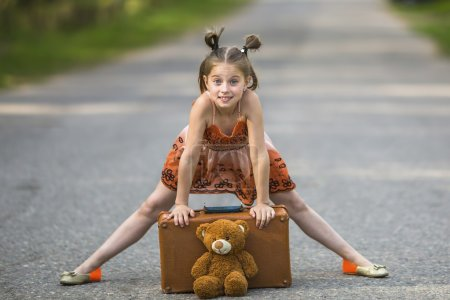 Photo for Little girl on the road with a suitcase and a Teddy bear. - Royalty Free Image