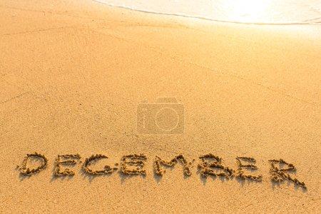 December - written on sandy beach