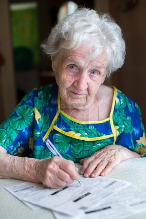 Photo for An elderly woman pays the utility bills. - Royalty Free Image