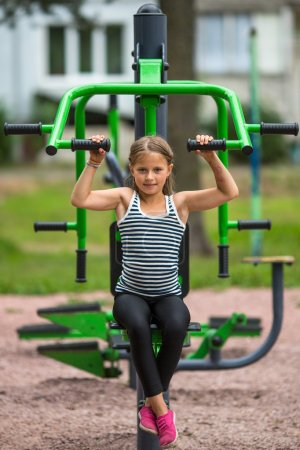 girl sitting on exercise equipment