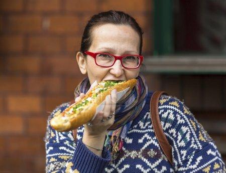 Young woman eating Polish fast-food