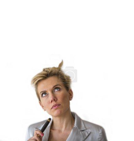 Photo pour La femme d'affaires avec le crayon regarde vers le haut. Espace pour le texte, d'isolement sur le fond blanc. - image libre de droit