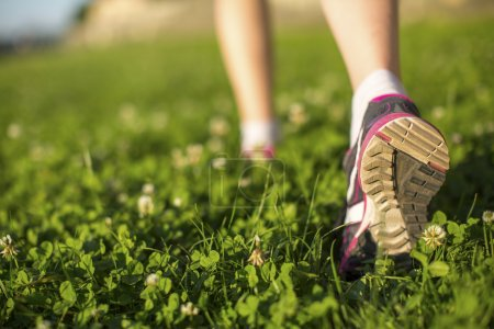 Foto de Hiker walking in the green grass outdoors, low angle close up of the foot. - Imagen libre de derechos