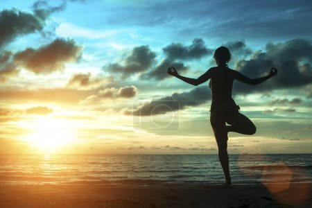 Silhouette of woman standing at yoga pose