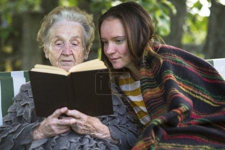 Photo pour Grand-mère et petite-fille lisant un livre assis dans le parc . - image libre de droit
