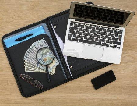 Photo pour Dossier d'affaires avec billets de dollars, ouvert l'ordinateur portable et le smartphone sur la surface de la table en bois . - image libre de droit
