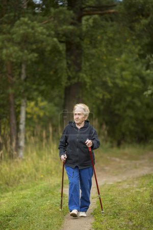 Mature woman walking in the green array