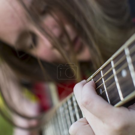 girl playing on guitar