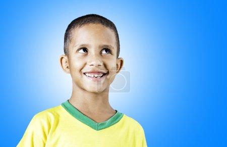 Little Brazilian boy smiling on blue background