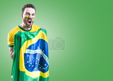 Man holding the Brazilian flag on green background