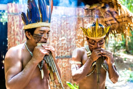 Native Brazilians playing wooden flute at an indigenous tribe in the Amazon