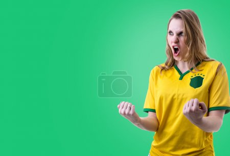 Brazilian female fan celebrating on green background