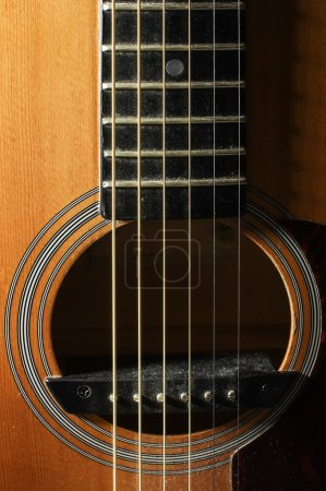 Close up of guitar resonant hole with rosette low key lighting