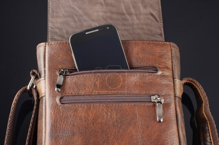 Mobile phone in the pocket of leather messenger bag