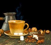 šálek kávy, cukroví, kávová zrna a skořice detail