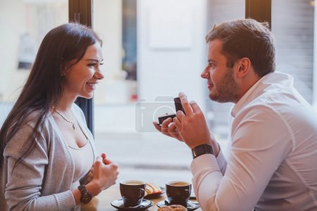 Happy couple in restaurant, man offers the ring, m...