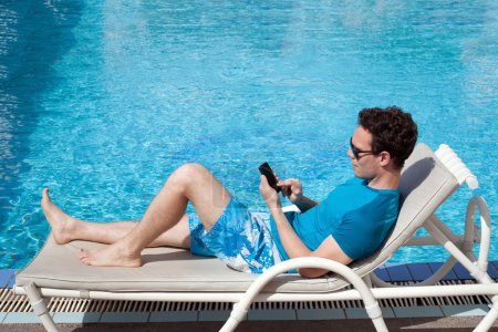 Photo pour Jeune homme à l'aide de smartphone près de la piscine dans l'hôtel de luxe - image libre de droit