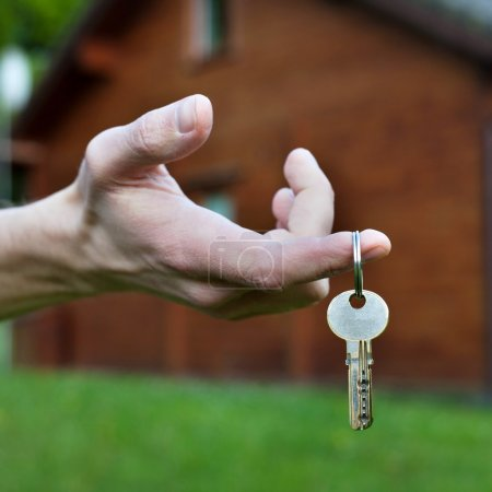 Photo for Buy cottage, real estate concept, keys in the hand - Royalty Free Image