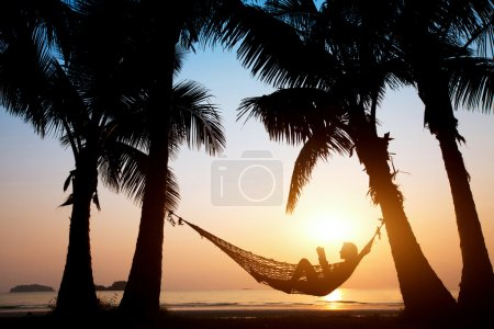 Photo for Beach vacations, silhouette of woman reading in hammock - Royalty Free Image