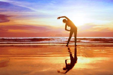 Photo pour Exercice sur la plage au coucher du soleil, belle silhouette de jeune femme - image libre de droit