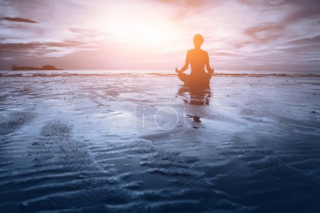 Photo for Woman practicing yoga on the beach at sunset - Royalty Free Image