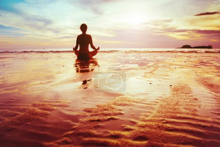 Photo for Enlightenment, silhouette of woman practicing yoga on the beach - Royalty Free Image