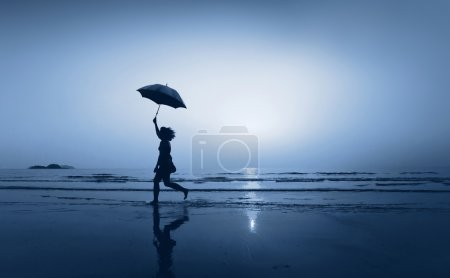 Photo for Small girl with umbrella on the sea beach at night. follow your dream - Royalty Free Image