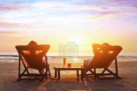 Happy couple enjoy luxury sunset on the beach duri...