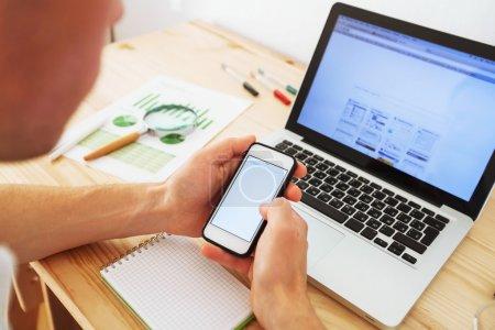Photo pour Homme avec smartphone à la maison, démarrage d'une entreprise - image libre de droit
