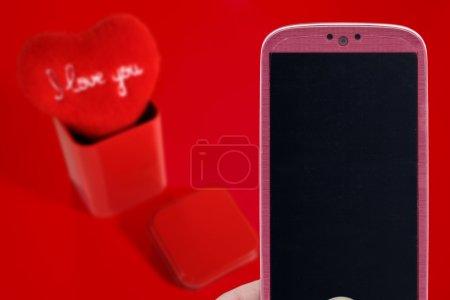 Photo pour Smatrphone rose et j'adore votre coeur sur fond rouge. Idée pour la Saint Valentin fête, amour, jour du père ou de la mère, amour apps, Internet, Articles et autres. - image libre de droit