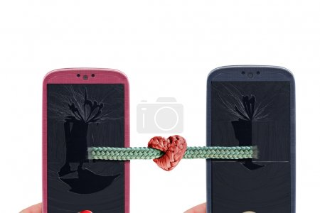 Photo for Blue and pink smartphones and rope with tied knot with a heart shape coming out from a broken glass and lcd . Idea for Valentines Day messages, love, lovers, love apps, Internet, blogs and others. - Royalty Free Image