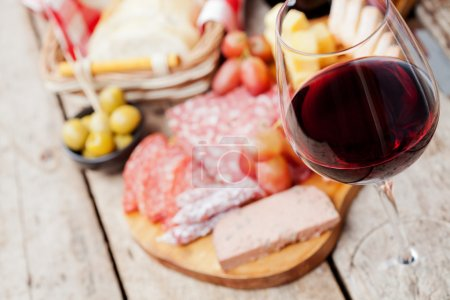 Glass of red wine with charcuterie assortment on t...