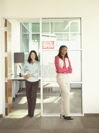 Businesswomen smiling for the camera in office space