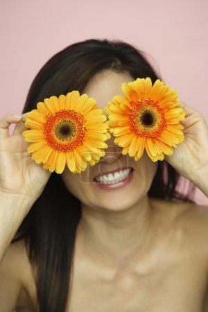 Asian woman holding flowers over eyes