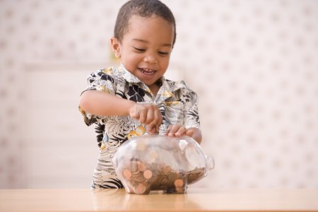 Young boy putting money in piggy bank