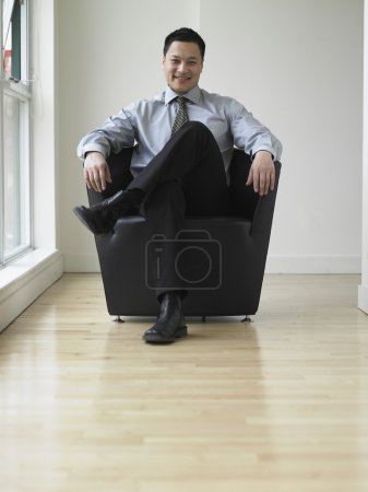 Young businessman sitting in an armchair