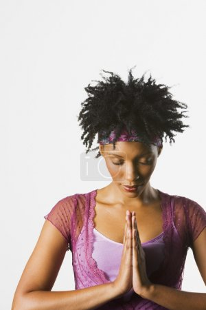 African woman with eyes closed and palms together in front of heart