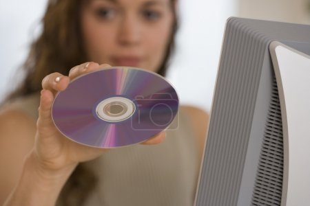 Hispanic woman holding up cd