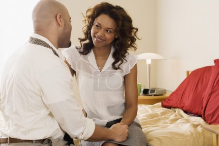 African couple smiling at each other on bed