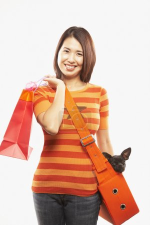 Asian woman holding dog and shopping bag